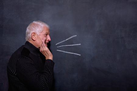 Portrait of senior man in front of blackboard