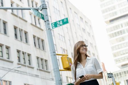 far away look: Business woman walking on street below Madison Street sign LANG_EVOIMAGES