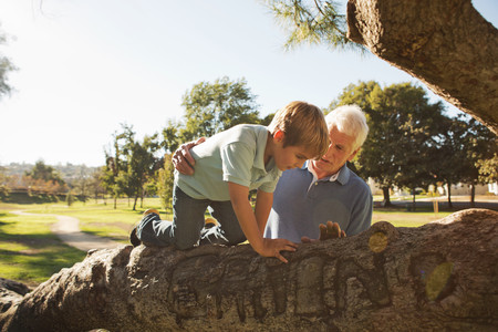 state of mood: Grandfather helping grandson to climb tree