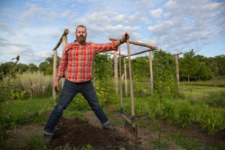 tiefe: Älterer Mann hält Rake auf Kräuterfarm