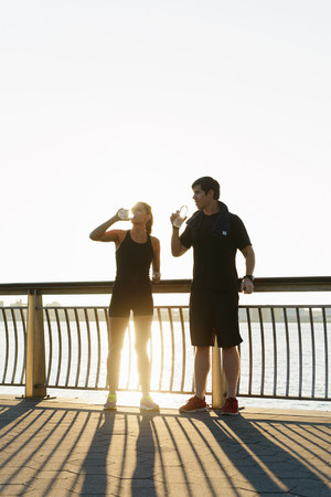 energy work: Jogging couple drinking water early morning