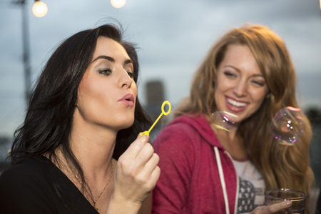Two female friends blowing bubbles at rooftop party LANG_EVOIMAGES
