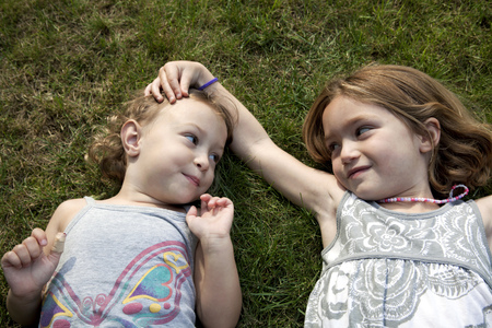 sweet grasses: Portrait of two young sisters lying on grass