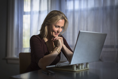 information age: Mature woman sitting at home using laptop