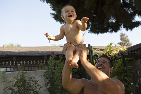 arms lifted up: Grandfather holding baby granddaughter LANG_EVOIMAGES