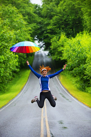 Teenage girl jumping with umbrella on road,Bainbridge Island,Washington,USA
