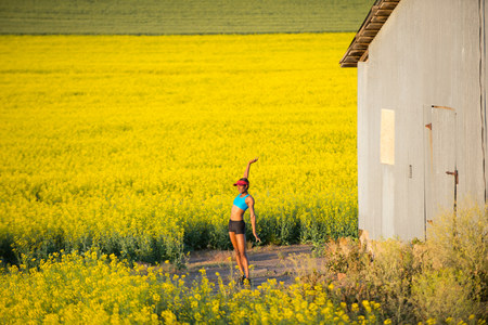 energy work: Young woman runner stretching in field of oil seed rape