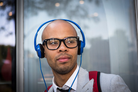 Portrait of young man with shaved head wearing headphones LANG_EVOIMAGES