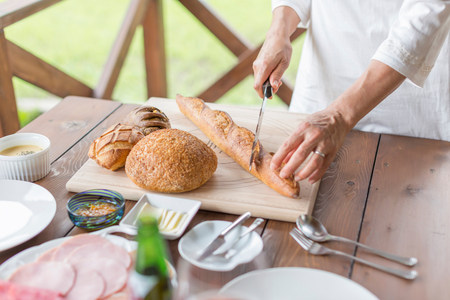 detoxing: Woman cutting baguette