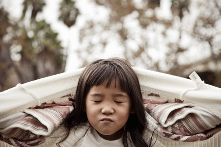 Portrait of young girl with eyes closed in park