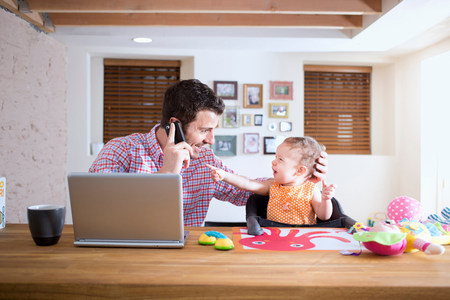worktops: Man and baby sitting at kitchen counter making phone call
