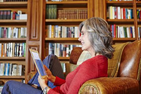 sit down: Mujer madura sentada en casa estudio usando tableta digital