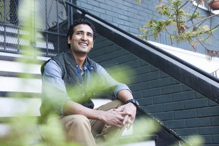 pantalones abajo: Retrato del hombre joven que se sienta en pasos LANG_EVOIMAGES