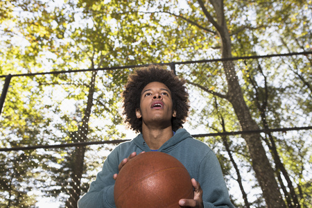 expect: Young man holding basketball