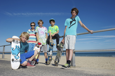 Portrait of five boys with skateboards at coast