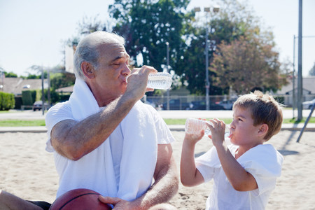 role model: Man and grandson drinking bottled water together LANG_EVOIMAGES