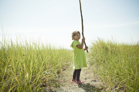 way out: Portrait of female toddler holding long stick
