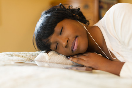 Young woman lying on bed listening to music on digital tablet