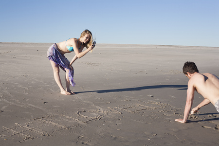 Couple writing message in sand,Breezy Point,Queens,New York,USA LANG_EVOIMAGES
