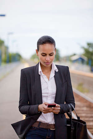 Businesswoman using cell phone on railway platform