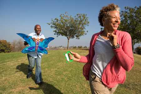 60 65 years: Senior couple running in park with kite LANG_EVOIMAGES