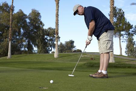 low self esteem: Portrait of mature male golfer taking shot on green