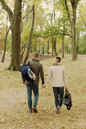 obscuring: Gay couple walking in park LANG_EVOIMAGES