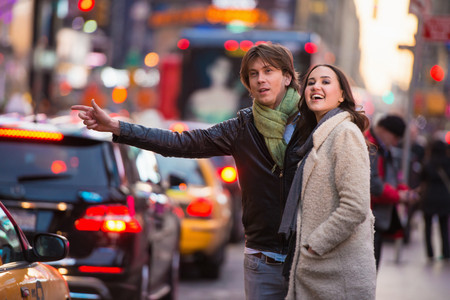 Young tourist couple hailing a cab, New York City, USA