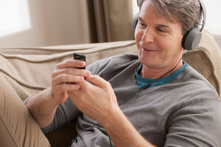 grays: Mature man wearing headphones using cell phone LANG_EVOIMAGES