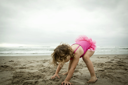 level playing field: Female toddler playing with sand LANG_EVOIMAGES