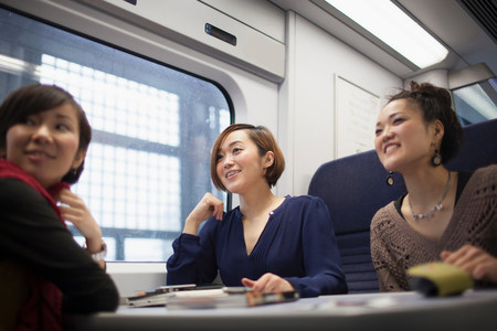 cropped out: Young women talking on train