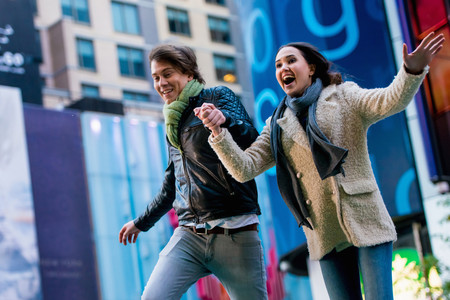 Young couple running on street, New York City, USA LANG_EVOIMAGES