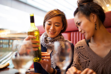 english ethnicity: Young women holding wine bottle LANG_EVOIMAGES