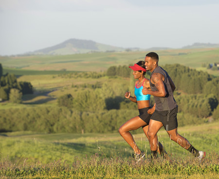 Man and woman running in landscape,Othello,Washington,USA