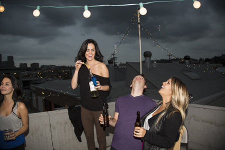 woman hanging toy: Young adult friends blowing bubbles at rooftop party