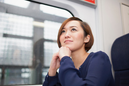 Young women daydreaming on train