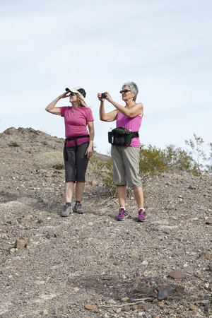 detoxing: Two senior female hikers looking and photographing view