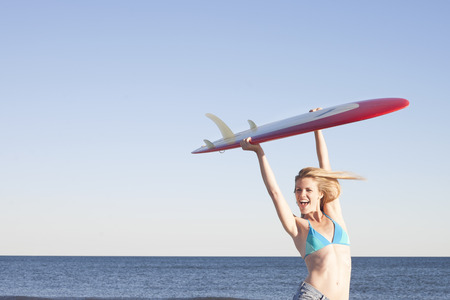 jesting: Young woman holding surfboard up,Breezy Point,Queens,New York,USA