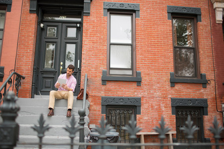 towerblock: Man sitting on step using digital tablet LANG_EVOIMAGES