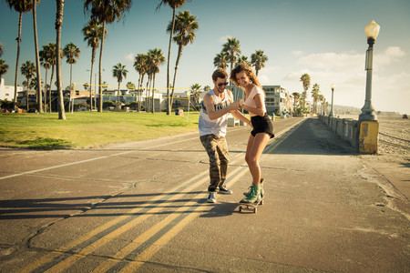 jesting: Young woman on skateboard at San Diego beach,boyfriend helping LANG_EVOIMAGES