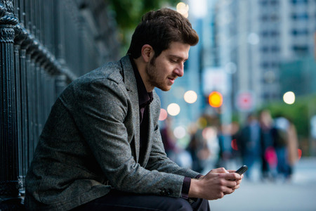 Young man waiting on city street, Toronto, Ontario, Canada