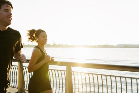 exerting: Jogging couple running along riverside early morning