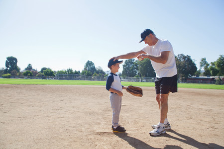 Grandfather and grandson on baseball field