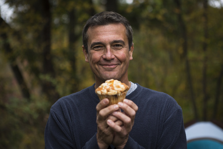 cropped out: Mature man in forest holding cupcake