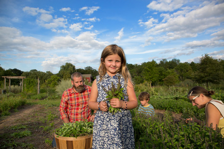 Portrait of girl holding bunch of leaves on family herb farm