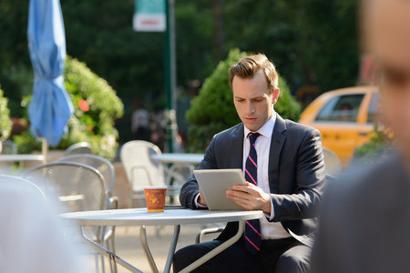 Businessman using digital tablet at sidewalk cafe