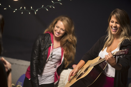 level playing field: Female friends enjoying guitar music at rooftop party