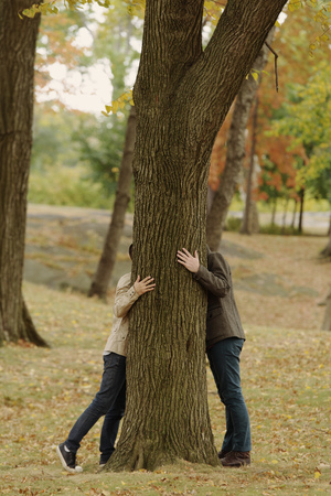 sexual anatomy: Gay couple hiding head behind tree trunk LANG_EVOIMAGES