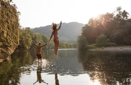 german ethnicity: Young couple jumping into river,Hamburg,Pennsylvania,USA