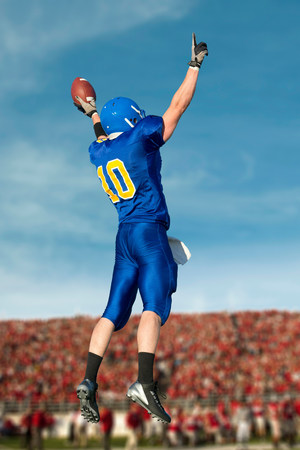 impulsive: American footballer jumping with ball